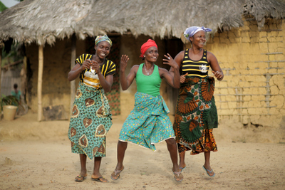 3 women dance in celebration at the news that the Government will support them in protecting their land from being grabbed by the palm oil company Equatorial Palm Oil.